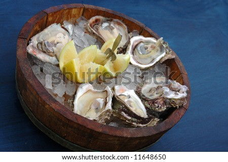 Fresh delicious cape rock oysters on ice with lemon and a fork in a wooden bowl on a blue table cloth in a restaurant - stock photo