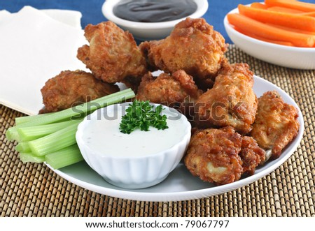 Fresh delicious chicken wings with dipping sauces, celery and carrots. - stock photo