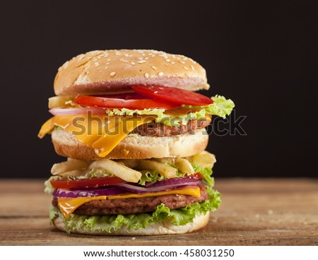 Fresh delicious double burger with cheese, tomato, onion, french fries and lettuce on wooden table and brown background with copy space - stock photo