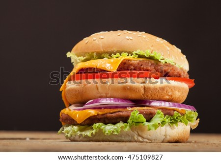 Fresh delicious double burger with cheese, tomato, onion, french fries and lettuce on wooden table and brown background with copy space