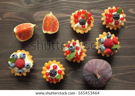Fresh delicious fruit tarts with cream and berries. - stock photo