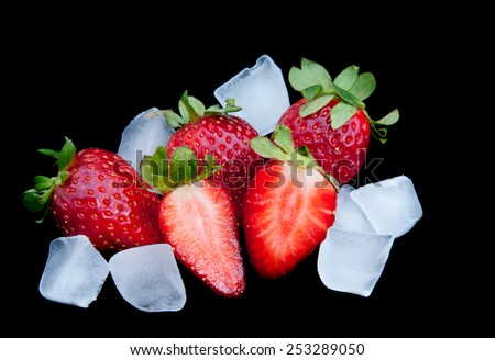 Fresh delicious red Strawberries on ice with black background. Strawberries are with green stems and leaves - stock photo
