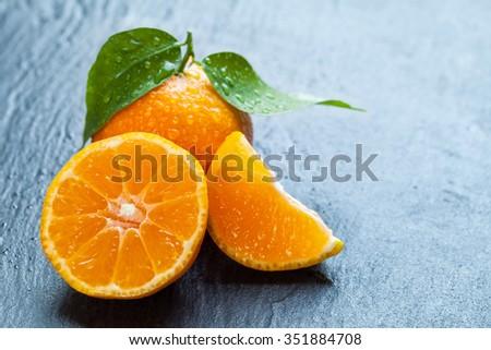 Fresh dewy mandarin placed on black stone. - stock photo