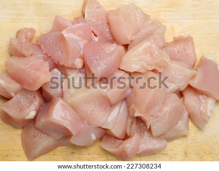 Fresh diced chicken breast meat on wooden chopping board. - stock photo