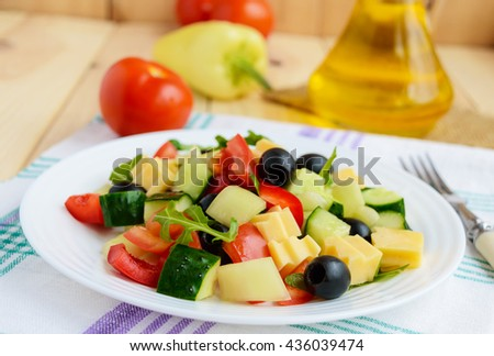 Fresh diet salad with cucumbers, tomatoes, olives cheese, bell peppers, arugula on a light wooden background