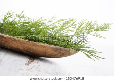 Fresh dill in wooden bowl on white wooden background. Aromatic culinary herbs, traditional rustic style.