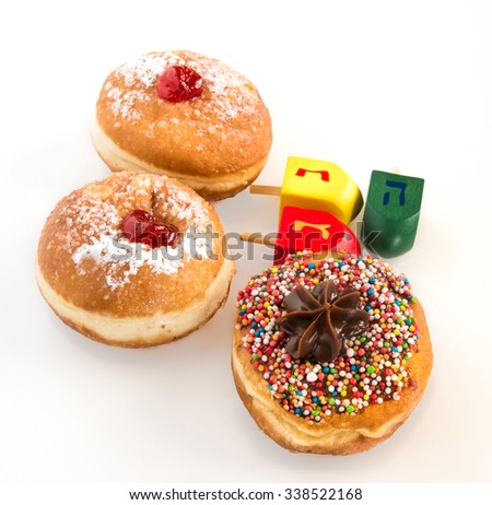 Fresh donuts and wood  dreidels for Hanuka  Jewish Holiday.  - stock photo