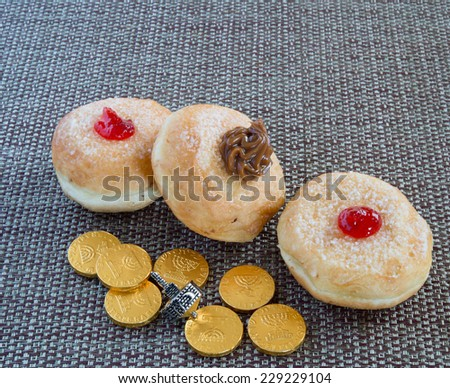 Fresh donuts with jam and chocolate, silver dreidel and coins  for Hanukkah celebration. - stock photo