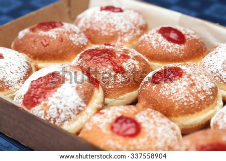 Fresh donuts with jam in the bakery for Hanukkah celebration. Isolated on a blue background - stock photo