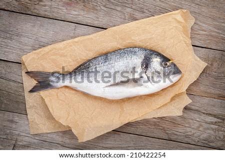 Fresh dorada fish on wooden table - stock photo