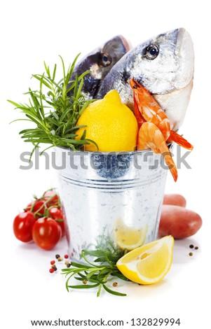 fresh dorada fish with vegetables over white - stock photo