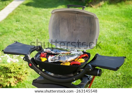 Fresh dorado fish and bell pepper grill cooking outdoors - stock photo