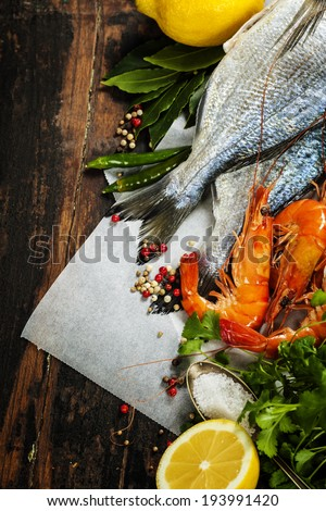 fresh dorado fish and shrimps on wooden board with ingredients- food and drink - stock photo