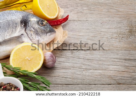 Fresh dorado fish cooking with spices and condiments on wooden table with copy space - stock photo