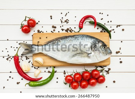 Fresh dorado fish on wooden cutting board with cherry tomatoes and chili peppers - stock photo