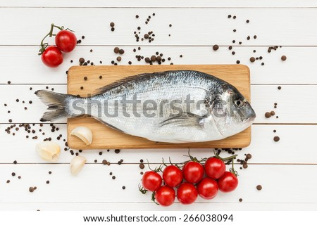 Fresh dorado fish on wooden cutting board with tomatoes - stock photo
