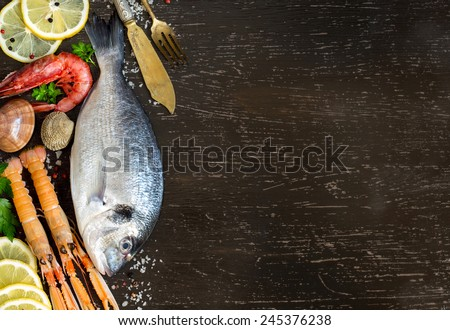 Fresh dorado fish, seafood and vegetables on a dark background - stock photo