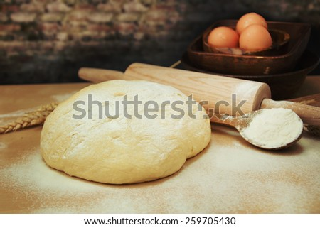 Fresh dough and rolling pin. - stock photo