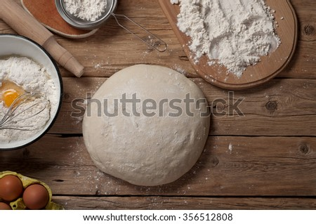 Fresh dough on a wooden table in a bakery with products for the preparation of dough closeup - stock photo