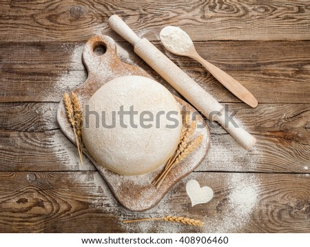 Fresh dough on cutting board with a rolling pin  the table.