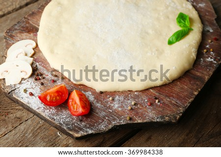 Fresh dough prepared for pizza with tomatoes and sliced mushrooms on a wooden board, close up - stock photo