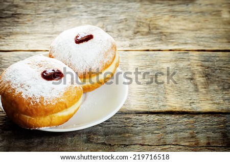 fresh doughnuts with jam on a dark wood background for Hanukkah. tinting. selective focus on the front donut - stock photo