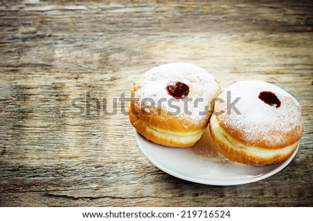 fresh doughnuts with jam on a dark wood background for Hanukkah. tinting. selective focus on the right donut - stock photo
