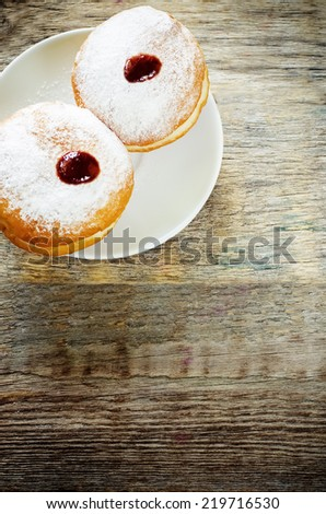 fresh doughnuts with jam on a dark wood background for Hanukkah. tinting. selective focus on the top donut - stock photo