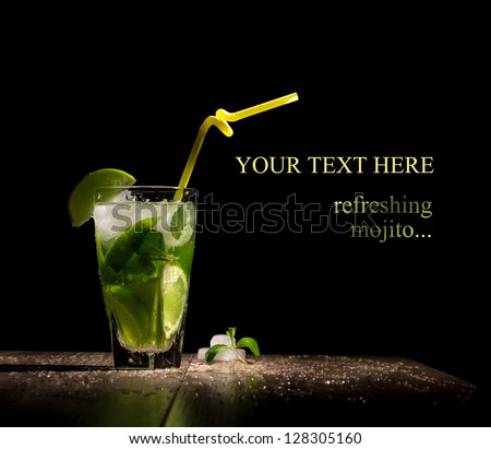 fresh drink with lime, mint and ice on wooden table on black background - stock photo