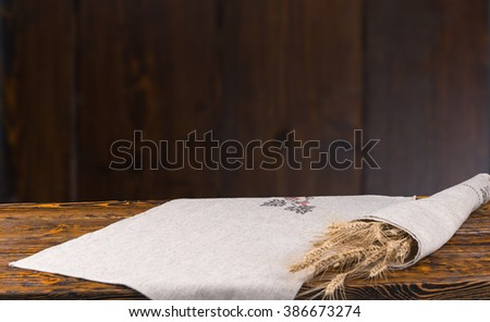 Fresh ears of ripe wheat wrapped in a cloth lying on a rustic wooden table with placement copy space for your wheat product or advertising - stock photo