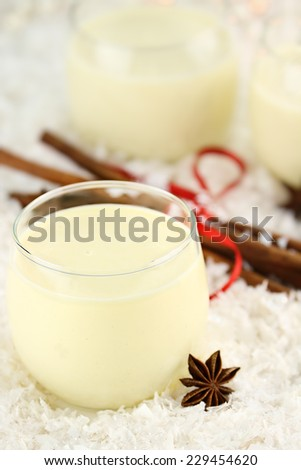 Fresh eggnog with cinnamon sticks and star of anise ready for the Christmas season. Extreme shallow depth of field. - stock photo