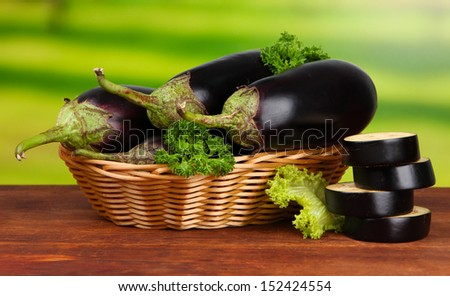 Fresh eggplants in wicker basket on table on wooden background - stock photo