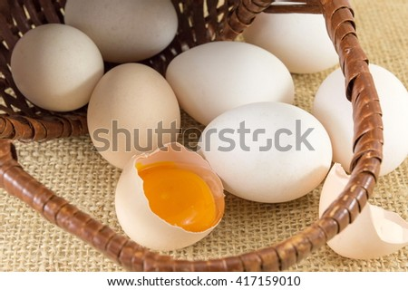 Fresh eggs falling out of a wicker basket - stock photo