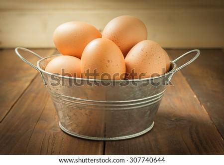 Fresh eggs in aluminium bucket on wood background , antique tone - stock photo