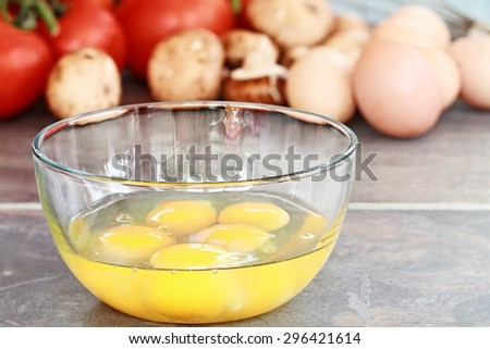 Fresh eggs with tomatoes, brown eggs, and mushrooms in background with shallow depth of field. - stock photo