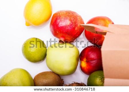 Fresh exotic fruits of orange juicy grapefruit yellow lemon ripe nectarine purple plum red pomegranate kiwi lime and green apple and paper pack lying on white background, horizontal picture - stock photo