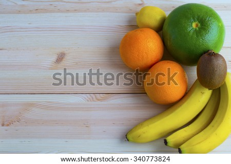 Fresh exotic fruits on wooden table background with copy space. Citrus fruit,  flat lay. - stock photo