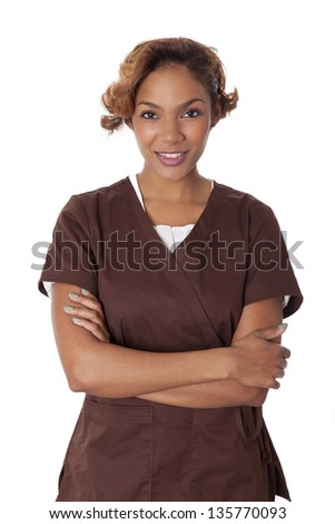 Fresh faced woman stands with arms crossed in scrubs, isolated on white background.
