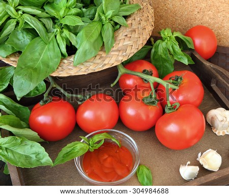 Fresh farmers tomatoes with basil and garlic on kitchen table wood background. Natural ingredients for cooking of a fresh tomato sauce  - stock photo