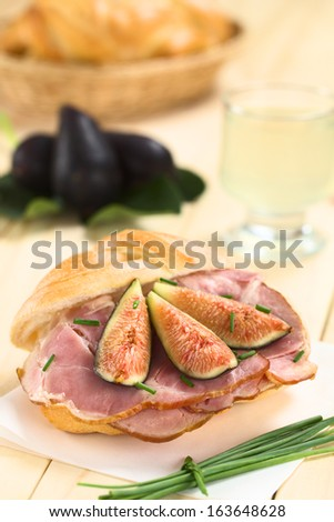 Fresh fig slices on smoked ham sandwich garnished with chives on sandwich paper (Selective Focus, Focus on the middle of the sandwich) - stock photo