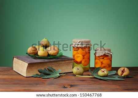 Fresh figs and Book on a wooden table - stock photo