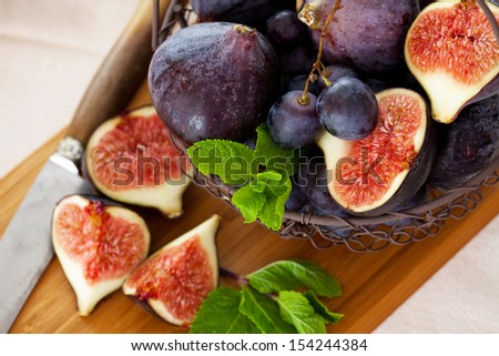 Fresh figs and grapes with green mint leaves - stock photo