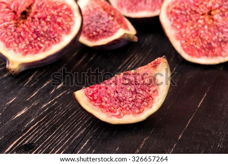Fresh figs cut into many slices on a dark wooden background