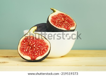 fresh figs in a bowl on wooden table, retro blue background