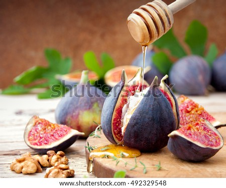 Fresh  figs with cheese and honey on wooden table.
