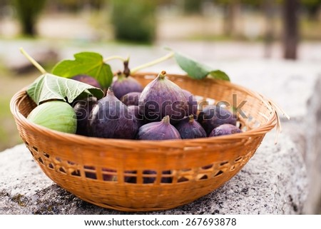 Fresh figs with leaves in basket, on stone table. Natural Fruit of garden - stock photo