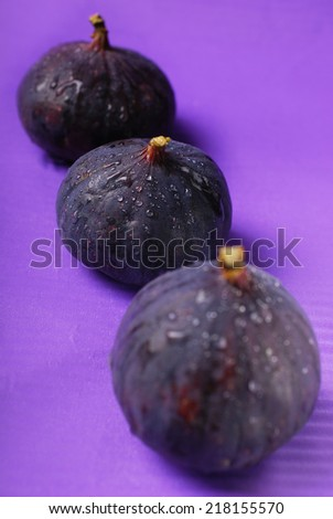 fresh figs with water drops in row on purple background