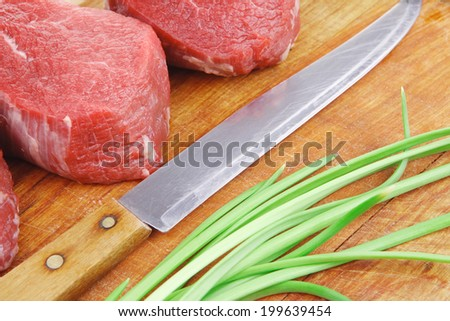 fresh fillet chops : raw beef fillet on wooden board with thyme and red hot dry pepper ready to prepare . isolated over white background - stock photo