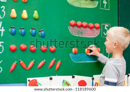 Fresh first year schoolboy student is standing before blackboard during mathematics lesson. - stock photo