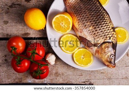 Fresh  fish and food ingredients on table - stock photo